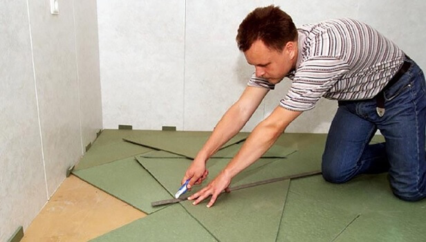 мастер подгоняет хвойную подложку под линолеум путем обрезки