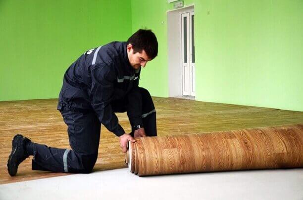 мужчина один раскатывает тяжелый рулон линолеума
