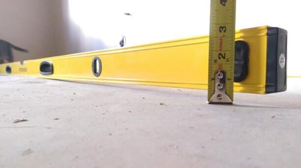 Проверяют ровность стяжки длинным уровнем и рулеткой
