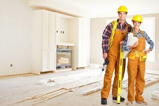 Стоят рабочие мужчина и женщина делающие ремонт пола