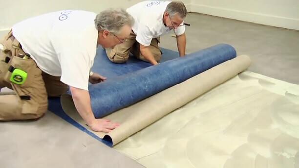 Двое мужчин раскатывают тяжелый линолеум
