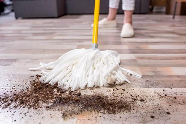 чистка линолеума от рассыпанной земли шваброй