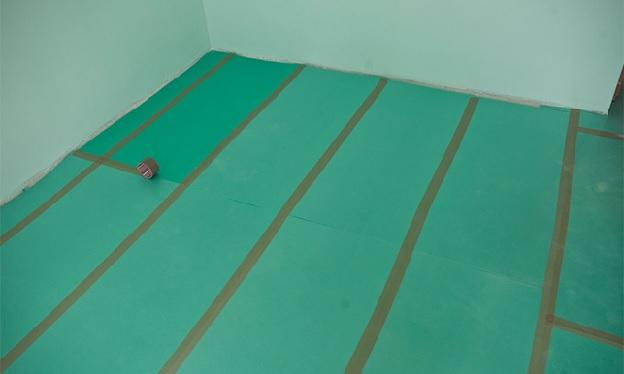 Соединение частей подложки скотчем под ламинат на бетонный пол