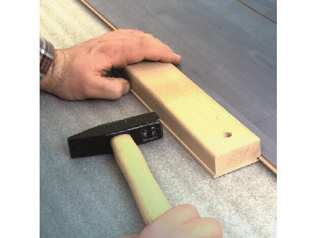 Подбивка ламината при помощи ударного бруска и молотка