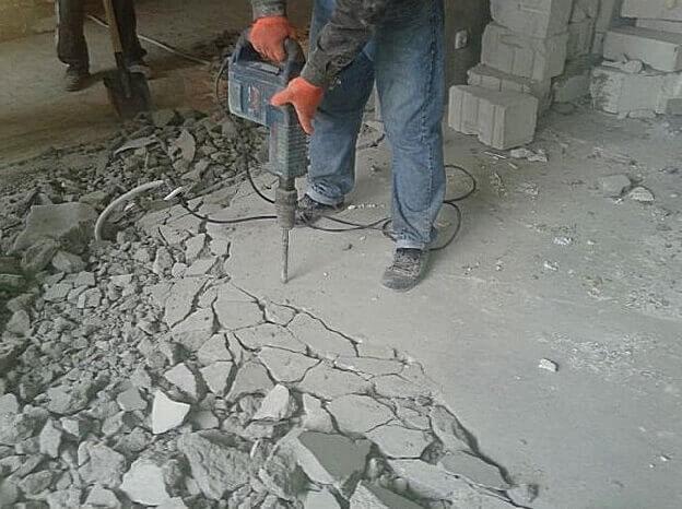 Рабочий ломает старую стяжку для укладки ламината по диагонали