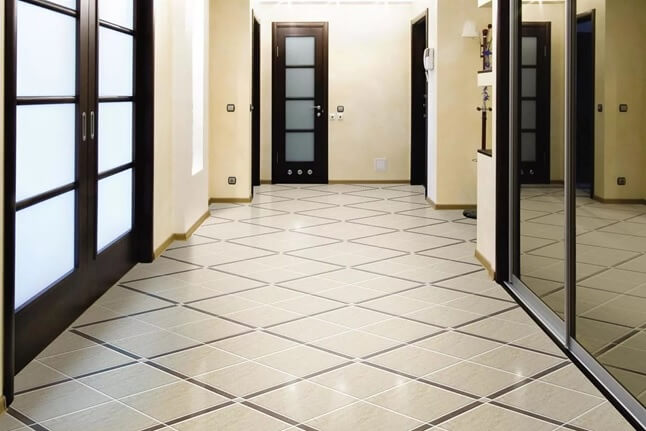 В прихожей на полу лежит износостойкий керамогранит квадратной формы
