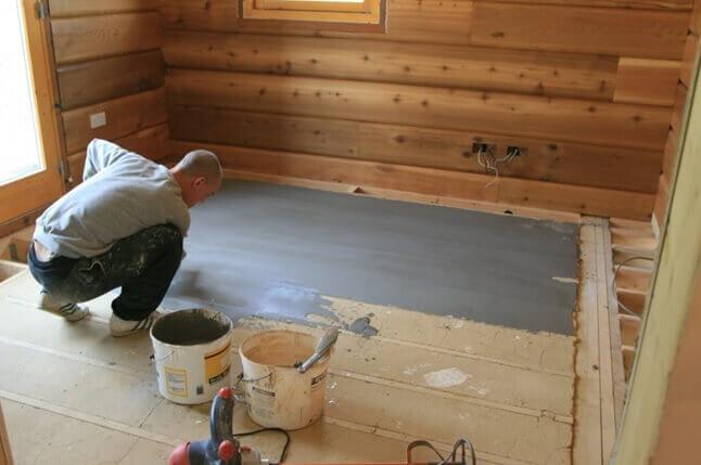 Нанесение самовыравнивающегося раствора на деревянный пол для укладки инфракрасного теплого пола под плитку